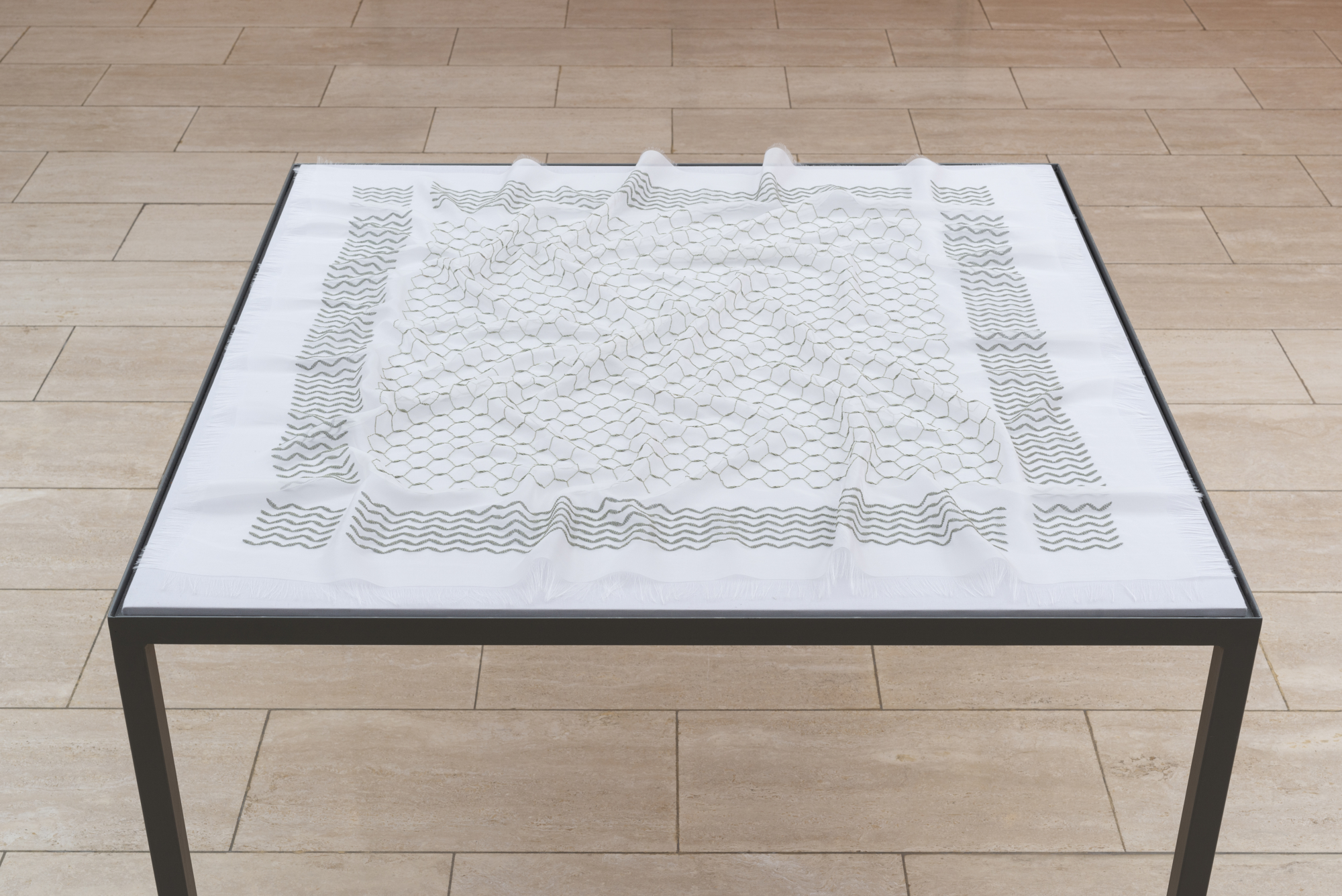 Keffieh II by Mona Hatoum looks like a typical Palestinian scarf, but if you look closer, you can see a sophisticated fabric of symbols